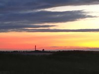 Sunset over Provincetown, Cape Cod, with the Pilgrim Monument visible in the distance