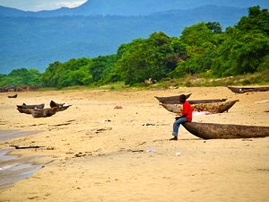 A man sitting on a boat at Kande beach in Malawi (© Martijn.Munneke, CC BY 2.0)