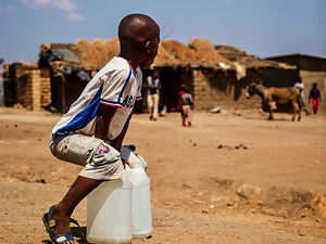 A young boy take a rest from carrying water home for his family. Photo taken in Dzaleka, Malawi