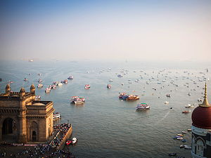 An aerial view of the Gateway to India with boats and fishermen in the background